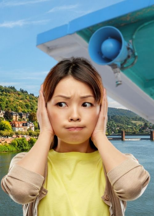 Girl annoyed by loudspeaker audio guide on river boat trip